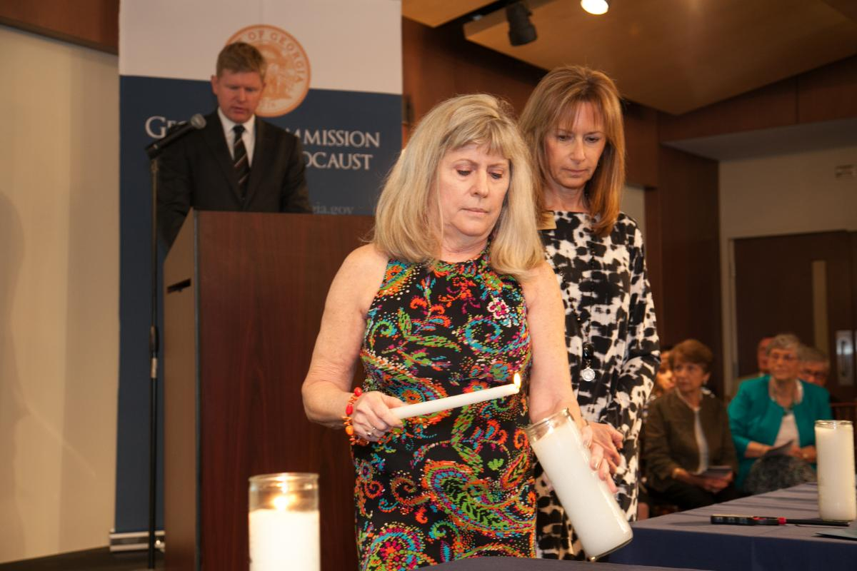 Karen Daniel lights a candle in memory of her mother, Holocaust survivor Aaltje de Vries Schappell
