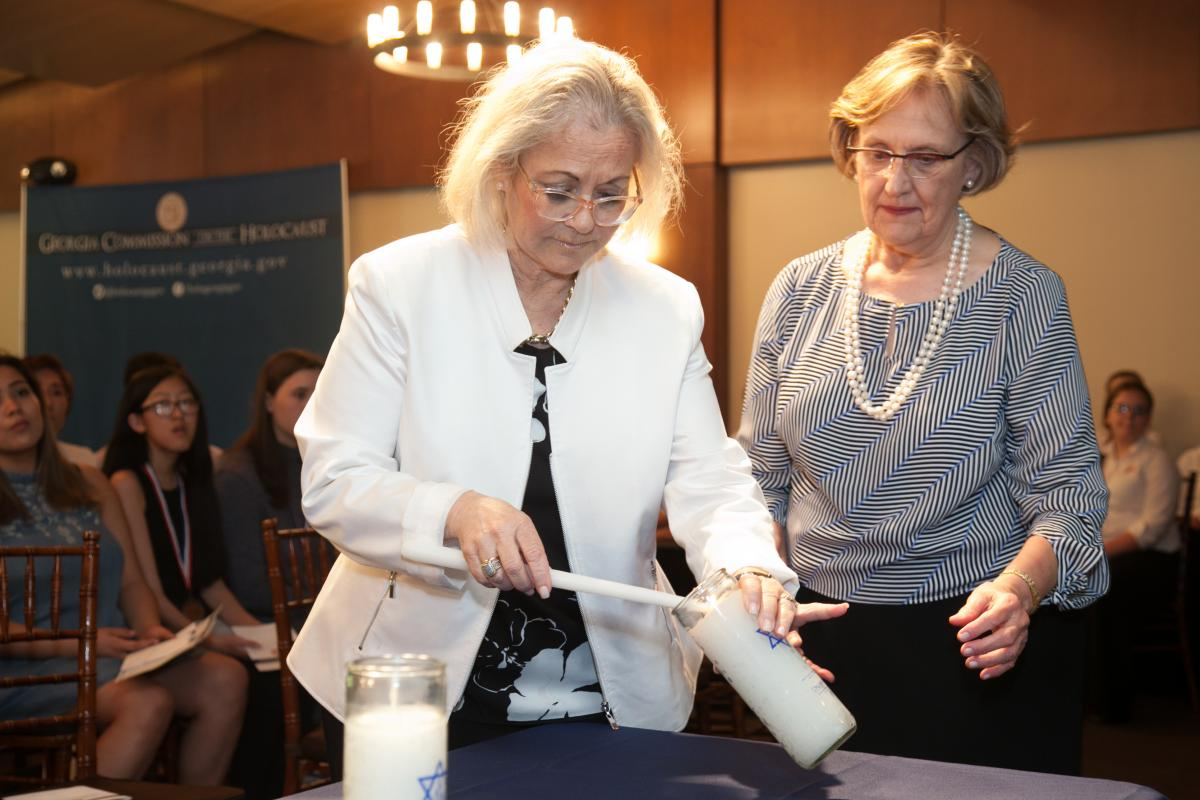 Ambassador Judith Shorer lights a candle in honor of her parents, Holocaust survivors George and Eva Vernai