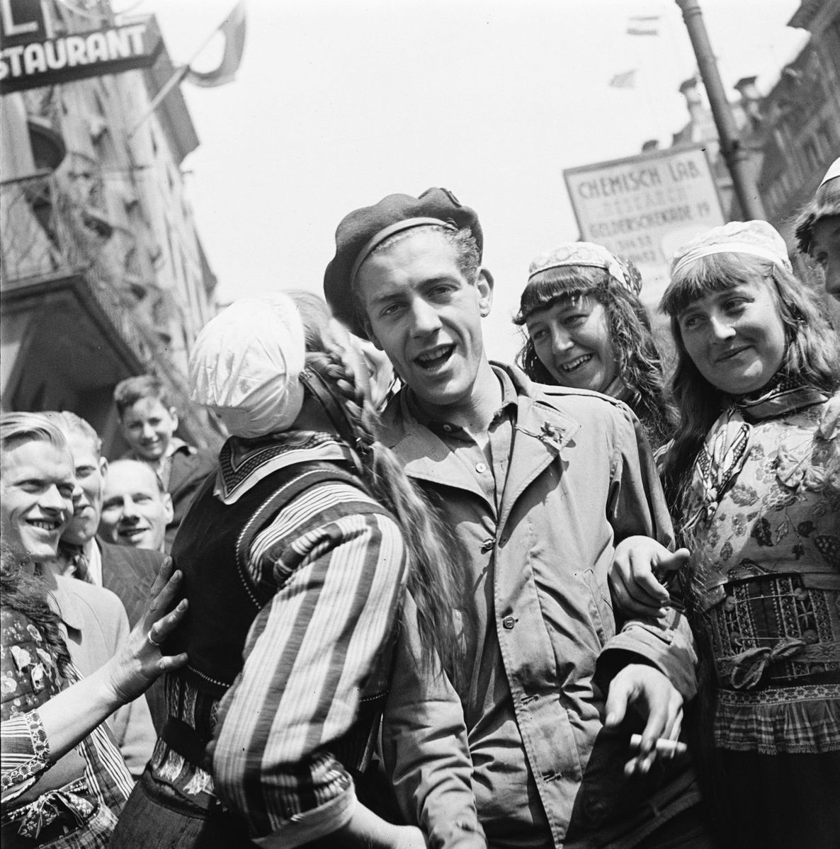 Young Canadian soldier flanked by Dutch women celebrating liberation.